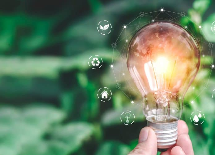 Imagem mostra um fundo verde folha; à frente, uma mão segura uma lâmpada acesa e, ao redor, há imagens de ícones que lembram sustentabilidade e meio ambiente