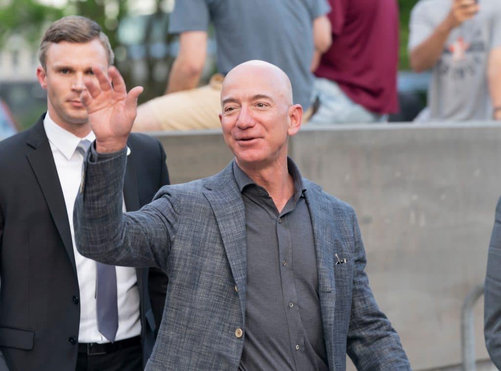 Imagem mostra Jeff Bezes, fundador da Amazon, acenando para às câmeras enquanto caminha em público.