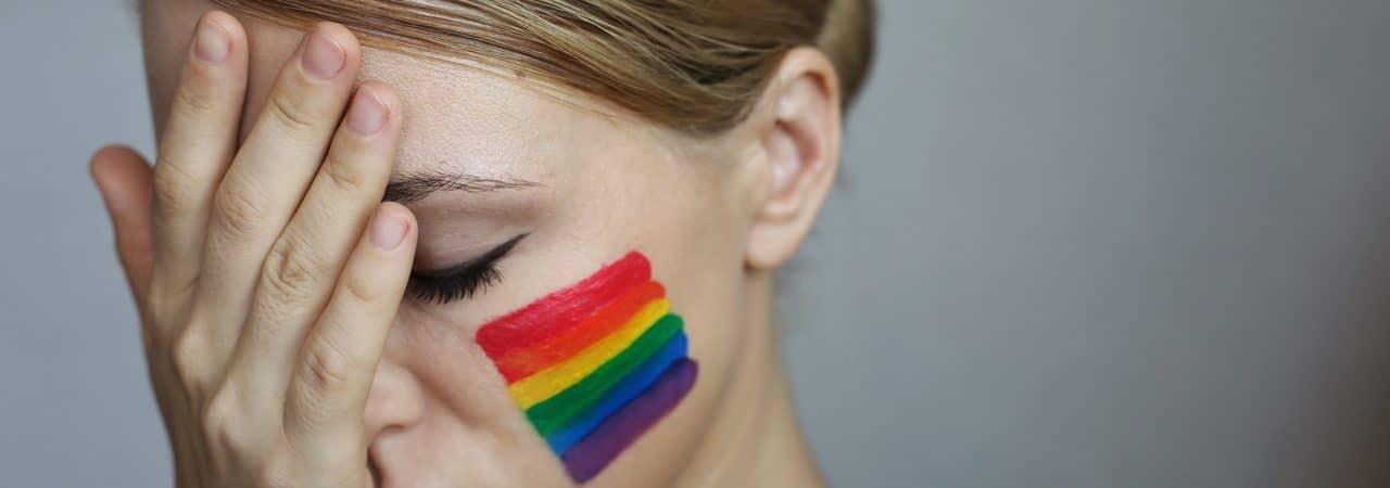 Mulher com semblante triste e uma bandeira LGBTQ desenhada em sua bochecha
