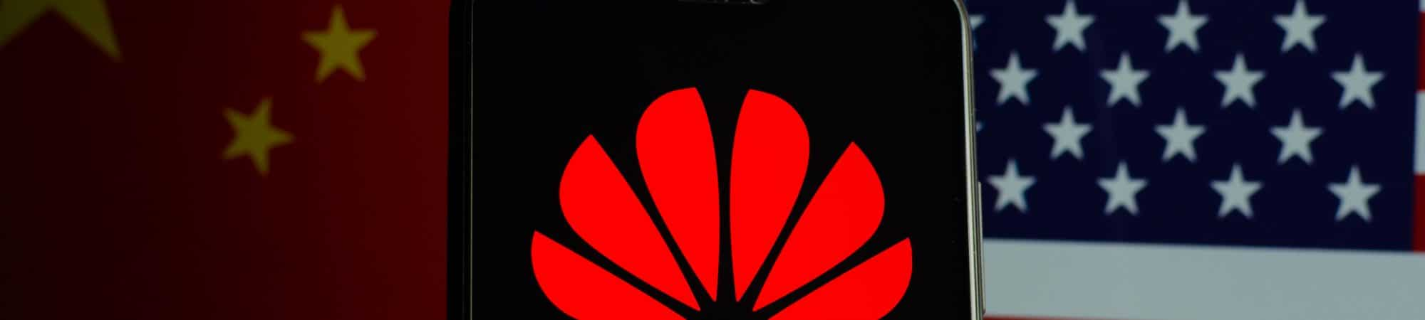 Huawei logo displayed on smartphone and flags of China and the United States in the background