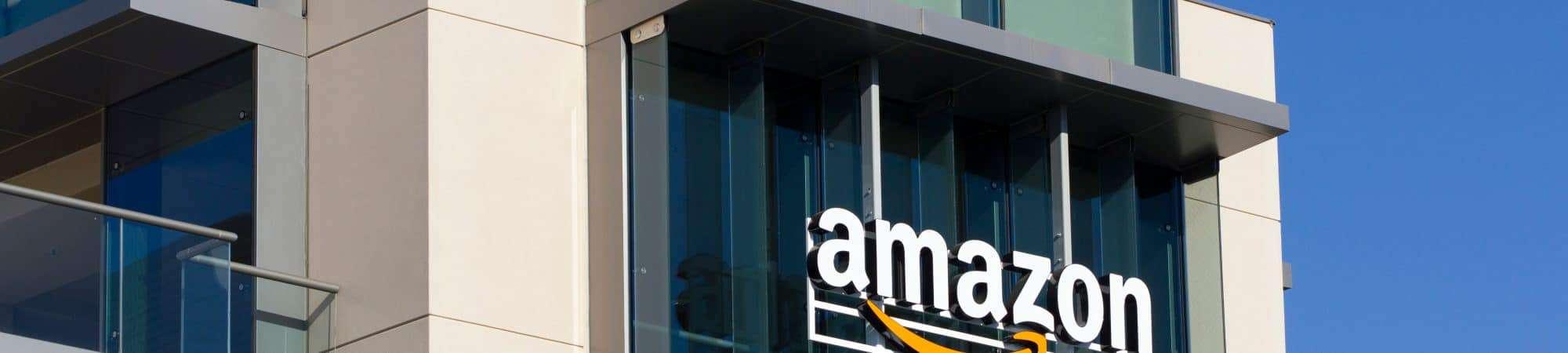 Imagem mostra a fachada de um prédio da Amazon, com o logotipo da empresa no topo.