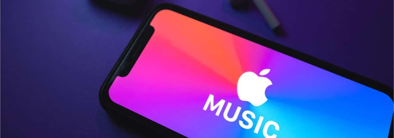 Logomarca do Apple Music é exibida em um smartphone, com dois fones sem fio posicionados ao lado em frente a um fundo azul