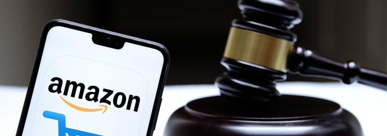 Logo da Amazon exibido em celular ao lado de um martelo de tribunal