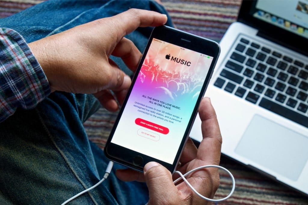 Imagem mostra um homem segurando um smartphone com a logomarca do Apple Music na tela: app receberá suporte a audio lossless e dolby atmos em junho