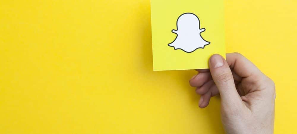 Em fundo amarelo, imagem mostra uma mão segurando um cartão que tem uma ilustração do fantasma, logomarca da rede social Snapchat