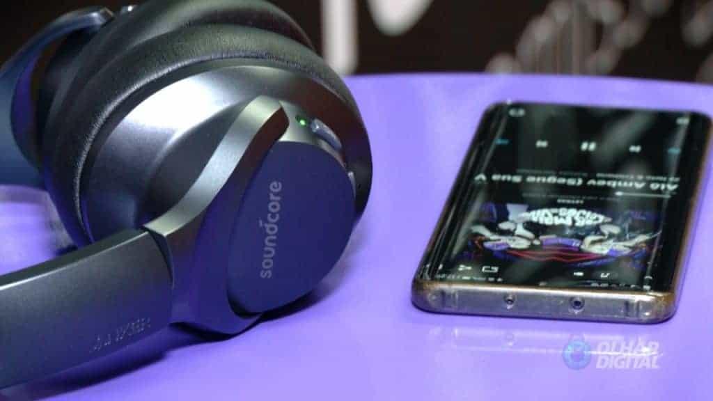 Imagem mostra a lateral do headset Soundcore Life Q20, da Anker, ao lado de um smartphone rodando um aplicativo de música