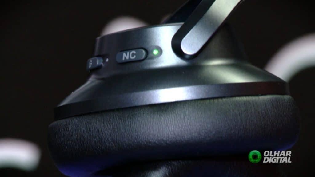 Imagem mostra a lateral de um headset, enfatizando o botão de acionamento do sistema de cancelamento de ruído do acessório