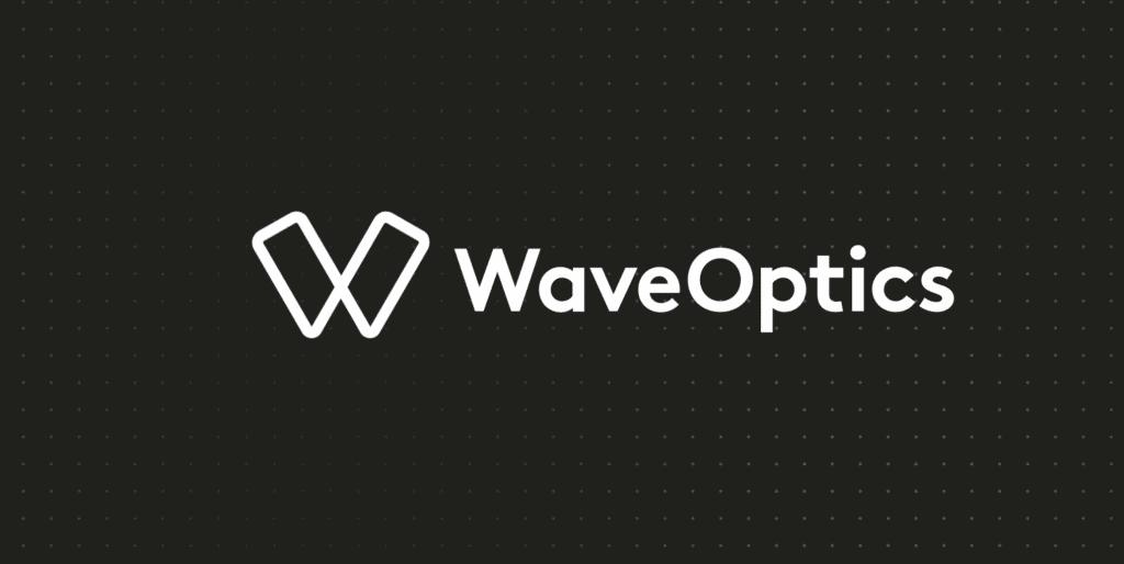 Imagem possui fundo preto com um padrão de pequenas bolinhas; à frente está o logotipo da marca WaveOptics, especializada em tecnologia para realidade aumentada