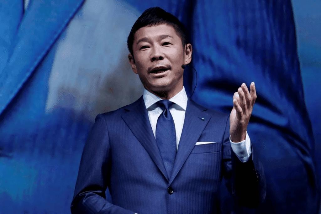 O bilionário japonês Yusaku Maezawa, que viajará para a ISS em dezembro de 2021, é exibido na imagem dando uma palestra, vestindo um paletó azul, com gravata azul escura e portando um microfone de orelha