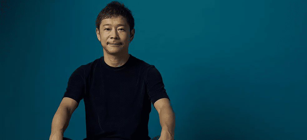 Yusaku Maezawa, bilionário japonês, é mostrado vestindo camiseta preta e calça jeans. Ele está sentado e com as pernas cruzadas, olhando para a câmera e sorrindo. Por trás dele, apenas um fundo azul escuro