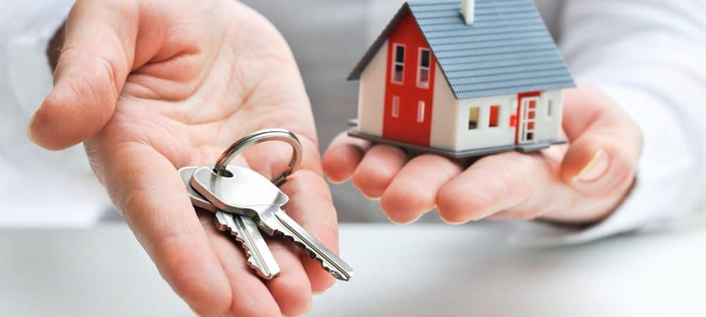 Mãos segurando chaves e uma casa em miniatura