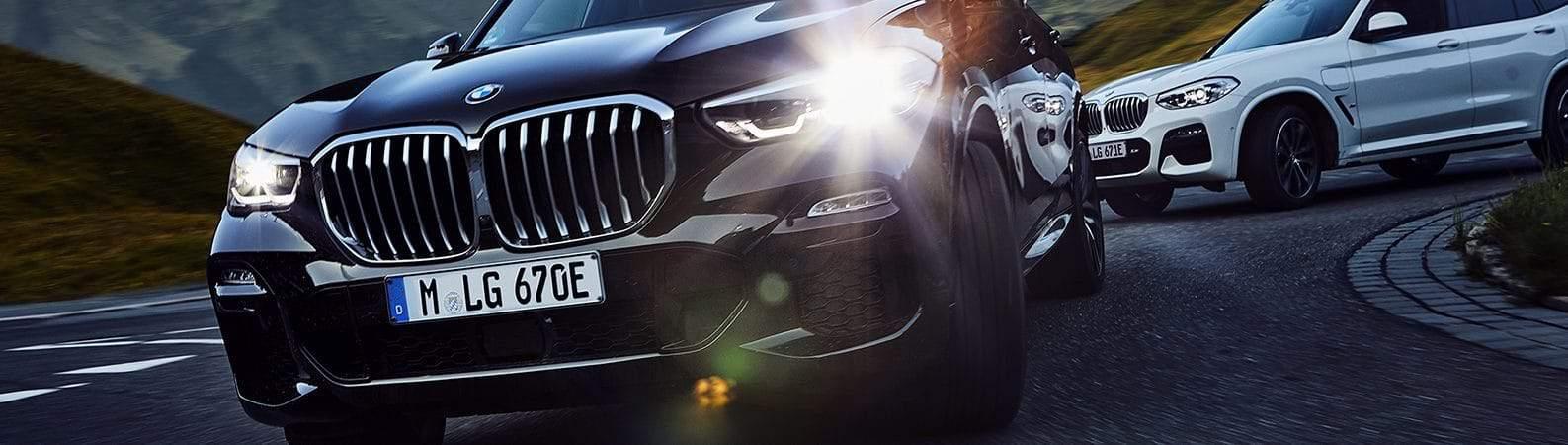 Imagem exibe BMW X3 preto em estrada com paisagem montanhosa.