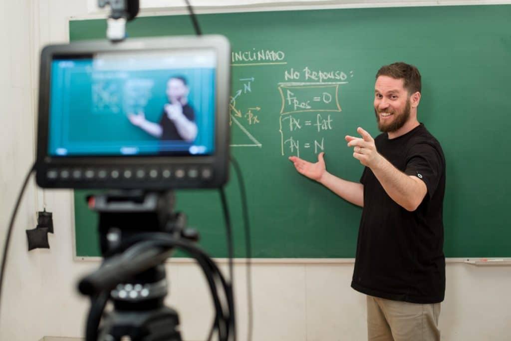 Marco Fisbhen mostrando anotações em uma lousa e apontando para uma câmera