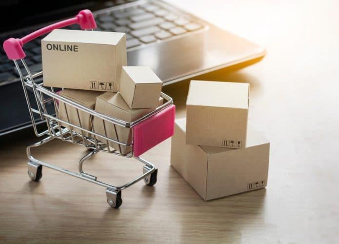 Carrinho de compras cheio de caixas ao lado de um notebook