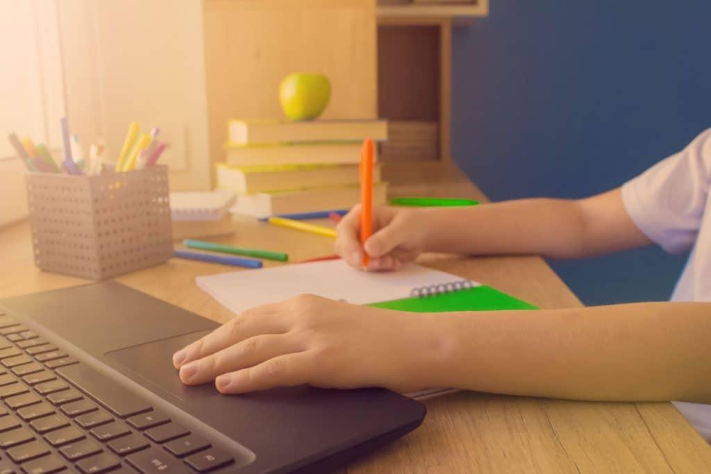Criança estudando em uma plataforma digital de uma edtech através de um notebook