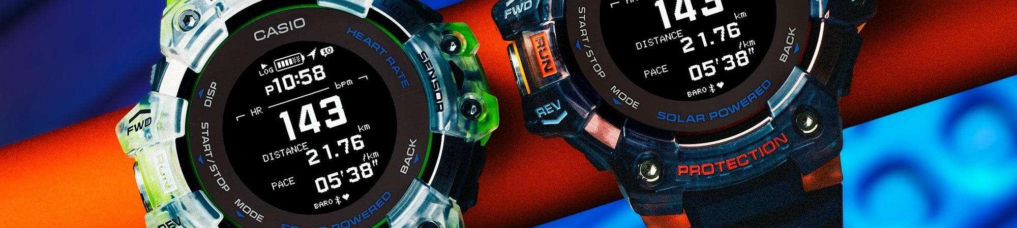 Imagem promocional mostra dois relógios GBD-H1000, da Casio. em um fundo azul neon. Um relógio tem a cor branca com detalhes verdes, enquanto o outro é preto com detalhes laranjas