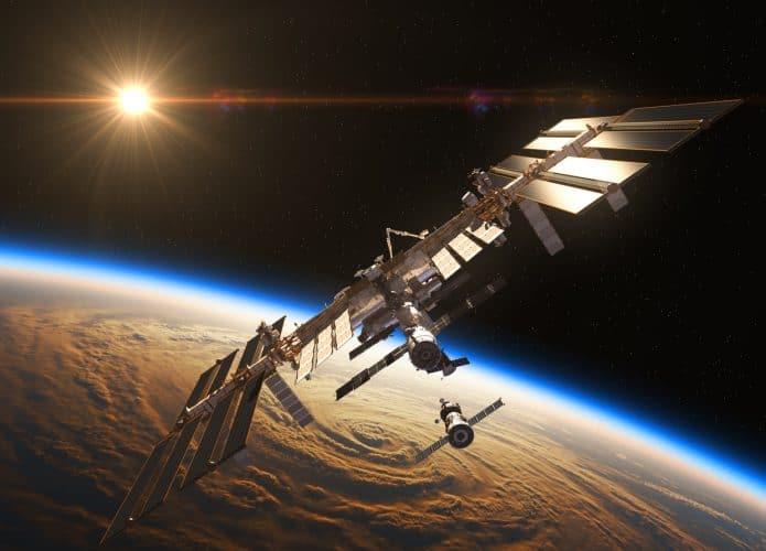 Imagem mostra a Estação Espacial Internacional, com a Terra e o Sol vistos no fundo