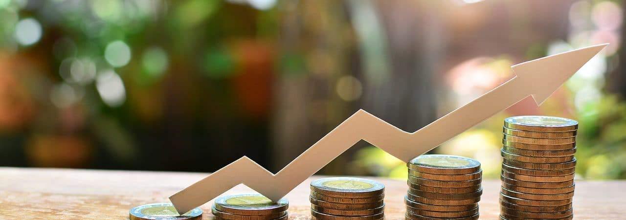 Imagem mostra cinco pilhas de moedas, uma ao lado da outra e cada uma de um tamanho, em ordem crescente; acima existe uma flecha que aponta o crescimento, para ilustrar um cenário de investimento positivo