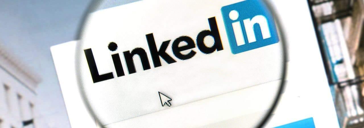 Imagem mostra o logotipo do LinkedIn aberto em uma página web; uma lupa está posicionada em cima do logotipo, aumentando seu tamanho
