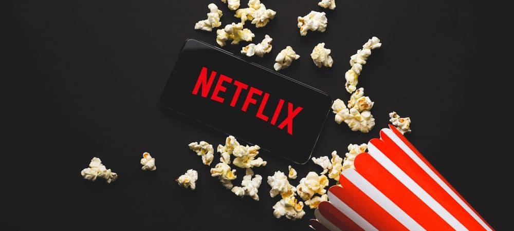 Logo da Netflix em um celular junto com um pote de pipoca