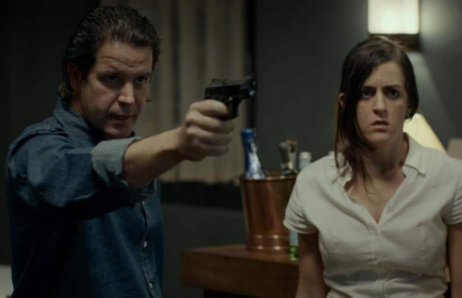 Murilo Benício empuña un arma en una escena en O animal cordial, junto a Juliana Paes