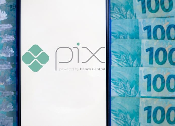 Image shows a smartphone screen displaying the logo of the Central Bank's instant payment system, the PIX; in the background several hundred reais bills appear.