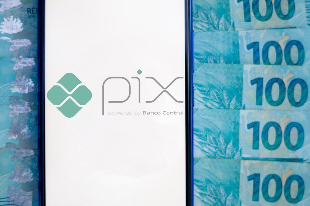 Imagem mostra a tela de um smartphone exibindo o logotipo do sistema de pagamentos instantâneo do Banco Central, o PIX; ao fundo aparecem várias notas de cem reais.
