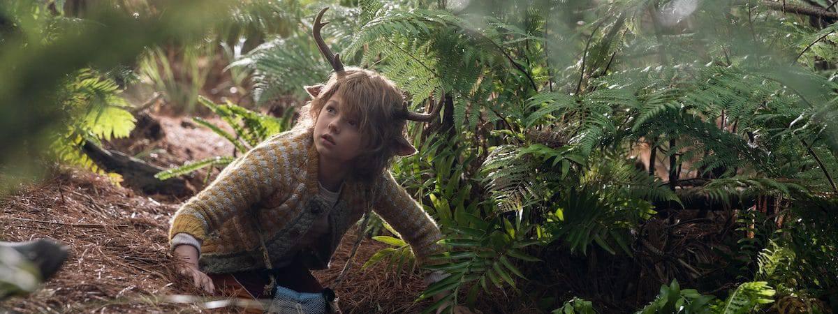 A imagem mostra o ator Christian Convery caracterizado como Gus, uma criança híbrida de humano e cervo, rastejando em uma floresta.