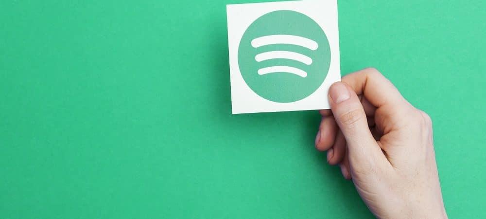 Imagem de fundo verde mostra uma mão segurando um cartão com o logotipo do Spotify