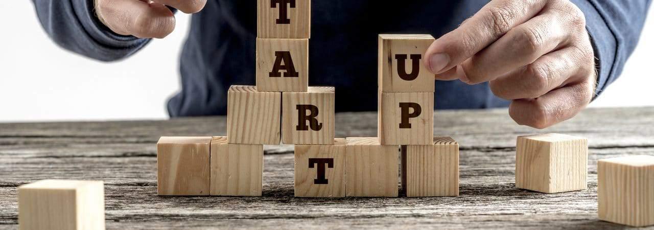 Imagem mostra mãos empilhando blocos em uma superfície reta, alguns dos blocos possuem letras que formam a palavra startup