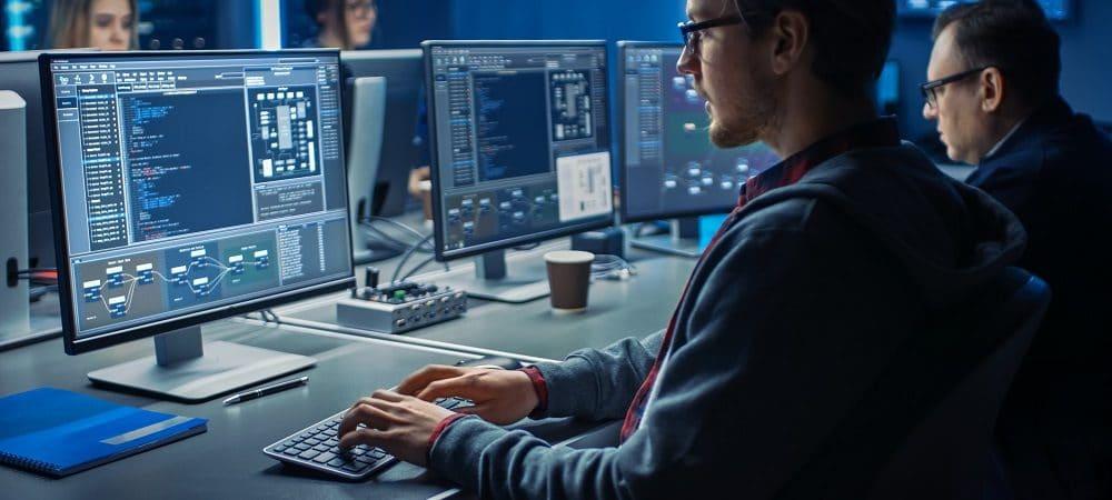 Imagem mostra homem sentado em uma mesa, digitando em um teclado de computador olhando para a tela do PC