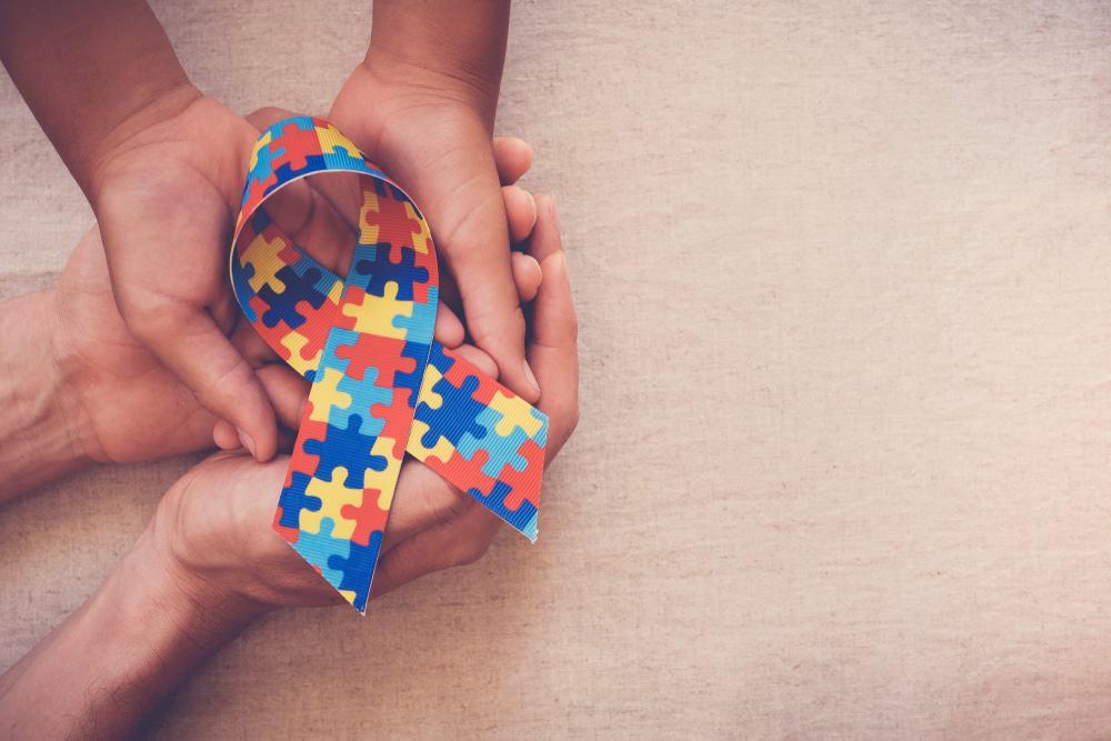 Mãos segurando uma fita estampada com um quebra-cabeça colorido