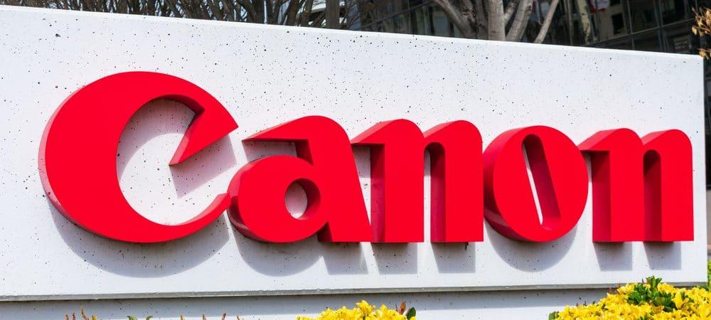 Imagem mostra o logotipo da empresa Canon, em um totem rodeado por plantas