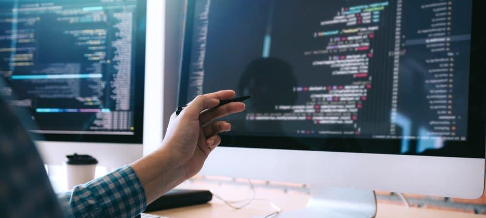 Imagem mostra um computador em cima de uma mesa; no monitor aparecem códigos de programação e, à frente, há uma pessoa apontando para a tela com uma caneta