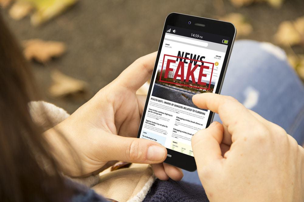 Imagem mostra uma jovem segurando um smartphone; na tela do dispositivo é possível ver a frase 'fake news'