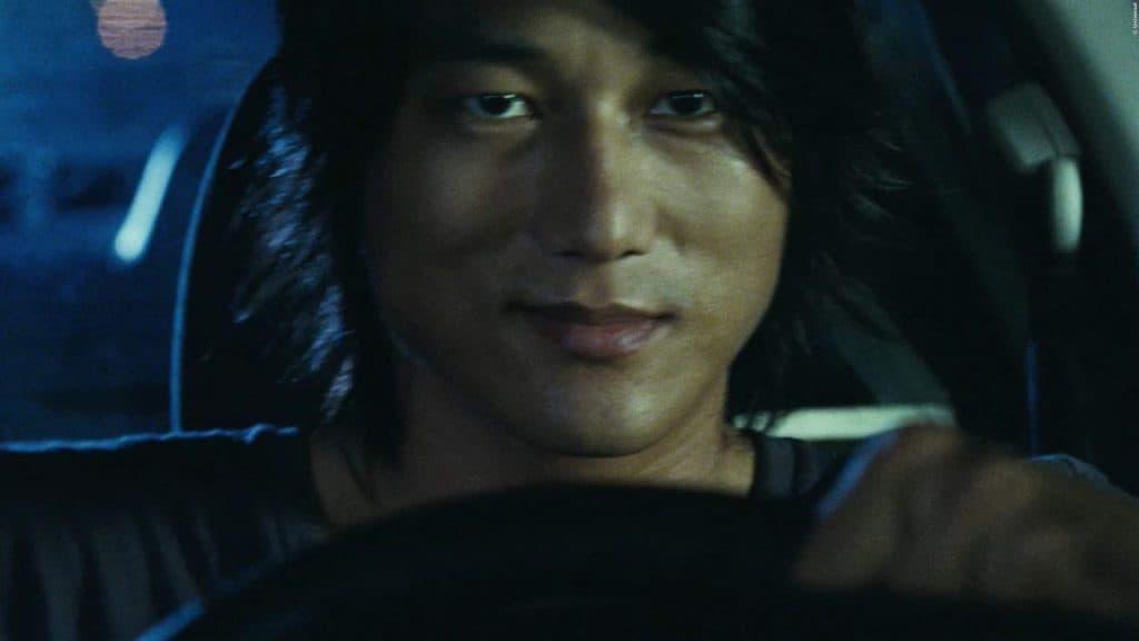 Han (Sung Kang) sosteniendo el volante en la escena de Rápido y Furioso: Desafío de Tokio.