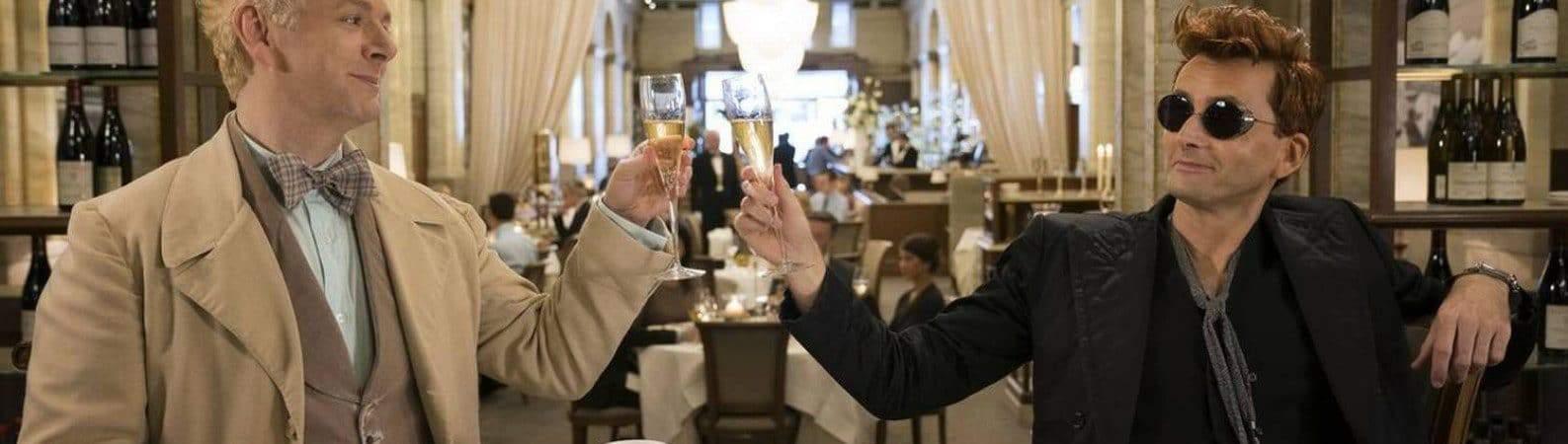 Em cena da primeira temporada, Michael Sheen (Aziraphale) e David Tennant (Crowley) aparecem brindando em uma mesa.