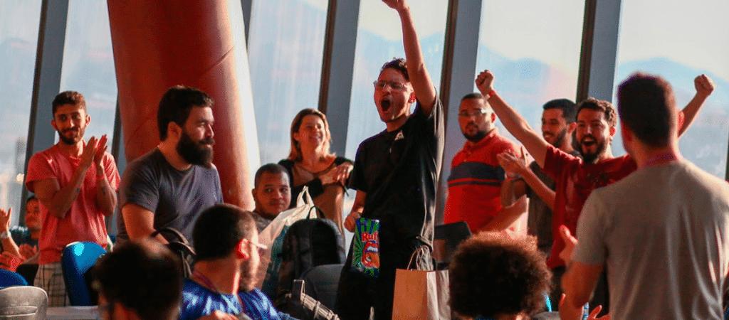 Imagem mostra um grupo de jogens comemorando durante o hackaton Hack Olimpic Games