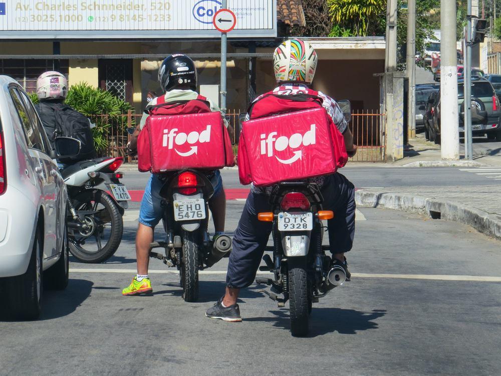Dois motoboys com mochilas doiFood