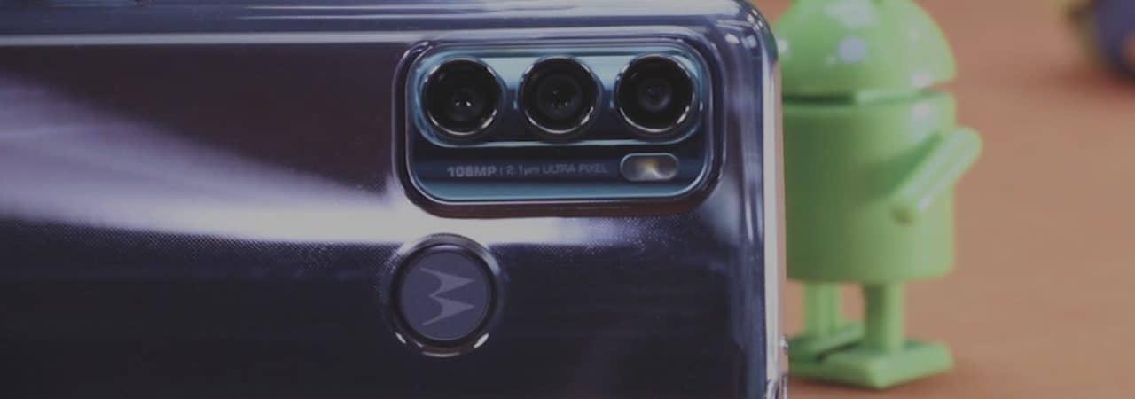 Imagem mostra a parte traseira do Moto G60, evidenciando suas três câmeras, eum boneco de corda do robô do Android ao fundo