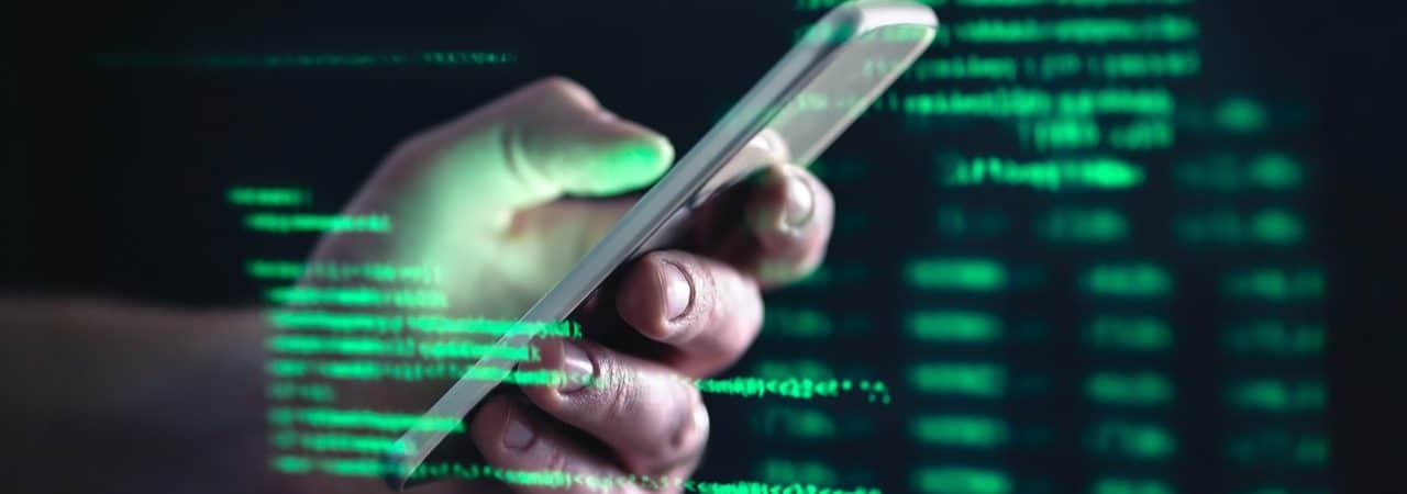 Imagem mostra uma mão segurando um smartphone e, ao redor dela, uma série de códigos e dados em fonte verde, simbolizando o acesso a informações privadas e golpes cibernéticos
