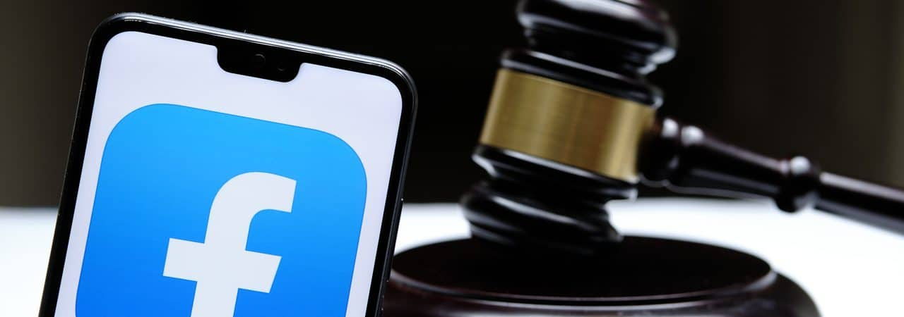 Facebook logo displayed on smartphone next to a courthouse gavel