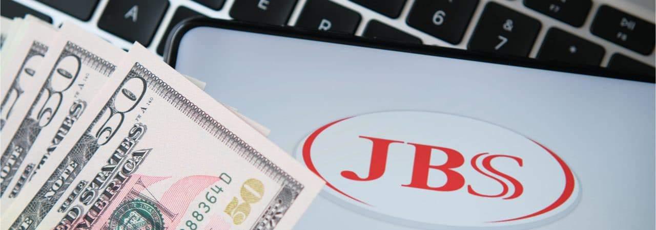 Imagem mostra a logomarca da JBS, ao lado de um maço de vários dólares