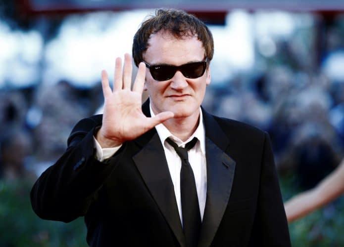 Quentin Tarantino de fraque e óculos escuro exibindo a palma da mão.