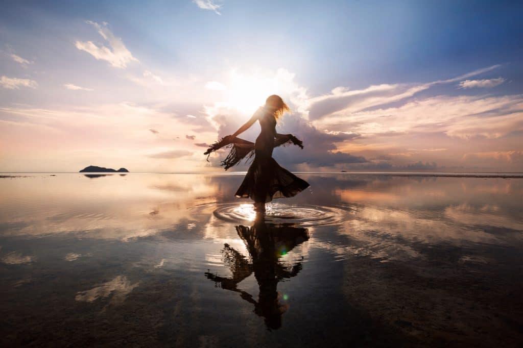 Imagem mostra uma mulher no lado, com a parte inferior da foto exibindo seu reflexo em um espelho d'água, simbolizando o princípio da homoquiralidade