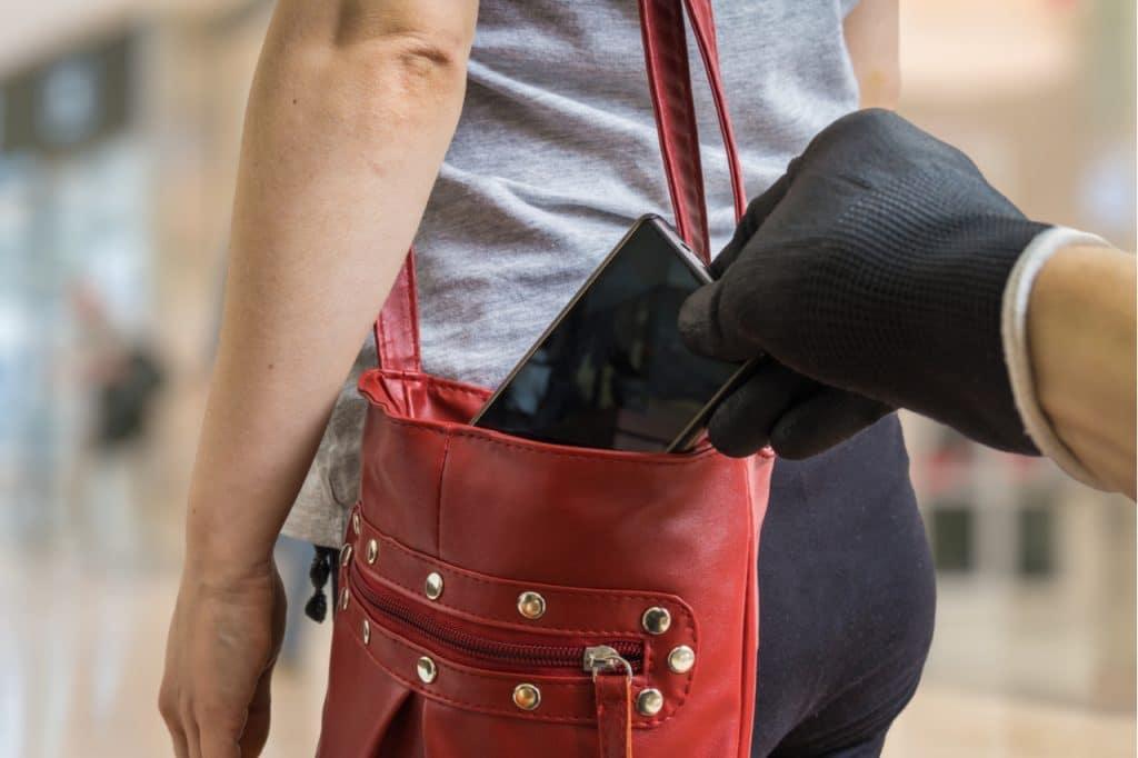 Imagem de uma mão roubando um celular de uma boa, evidenciando a prática de golpes financeiros