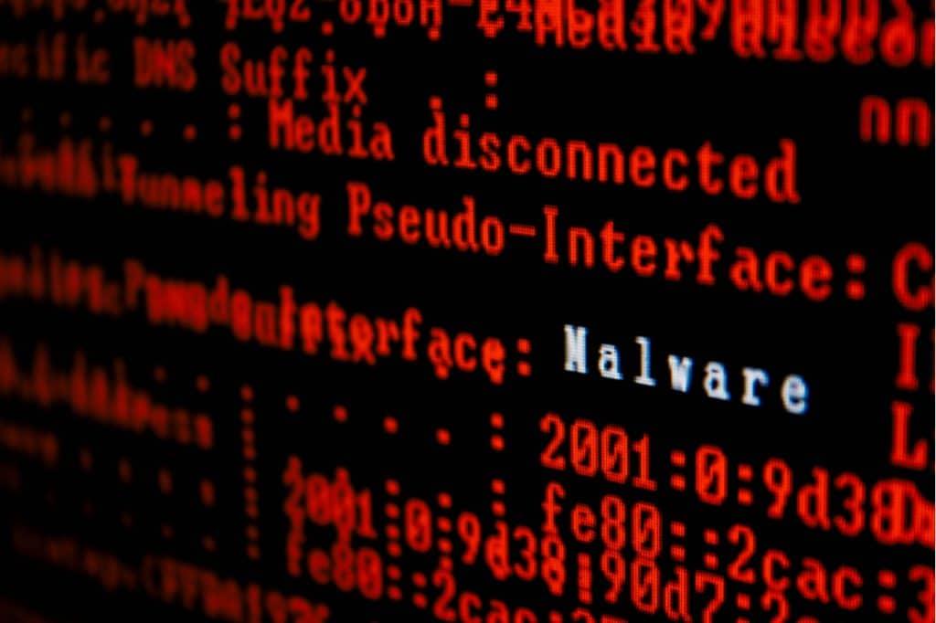 """Imagem mostra várias linhas de código em vermelho, com a palavra """"malware"""" escrita em branco."""
