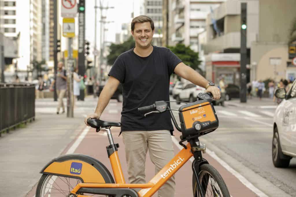 Foto mostra o fundador da Tembici, Tomás Martins, segurando uma das bikes da empresa em parceria com o Itaú; ao fundo está uma avenida