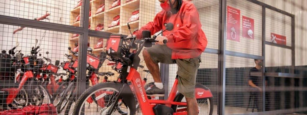 Imagem mostra um entregador uniformizado, montando uma bicicleta elétrica da Tembici em parceria com o iFood