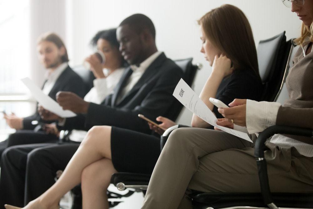 Cinco pessoas estão sentadas, uma ao lado das outras, esperando para serem chamadas para a entrevista de emprego.